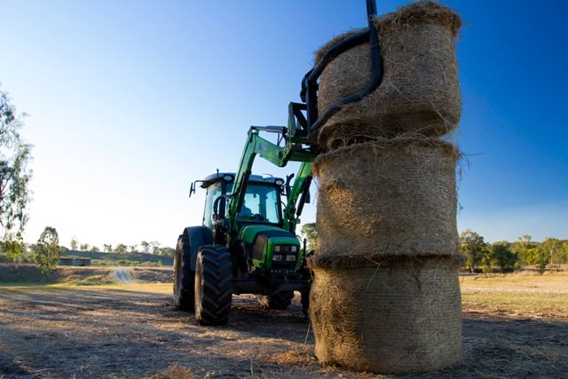 Stacking haybales with a tractor