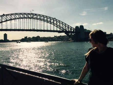 Georgie looking out to the Sydney Harbour Bridge at Sunset across the water from the back of the Opera House