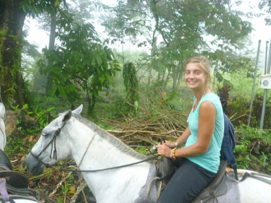 Volunteer on a horse in Costa Rican rainforest