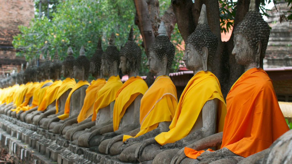 Buddha statues sit in a line at the Ayutthaya temple, dressed in bright orange robes