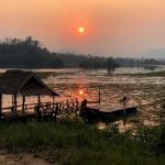 The sun sets and reflects in the lake at the elephant sanctuary in Laos