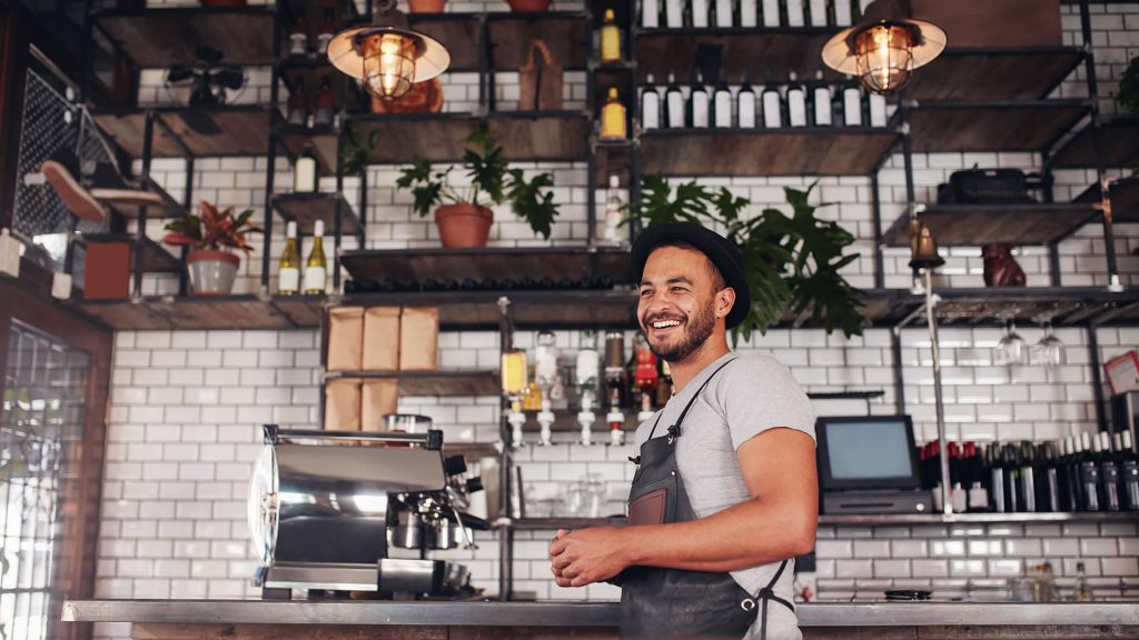 A worker laughs happily in his bar