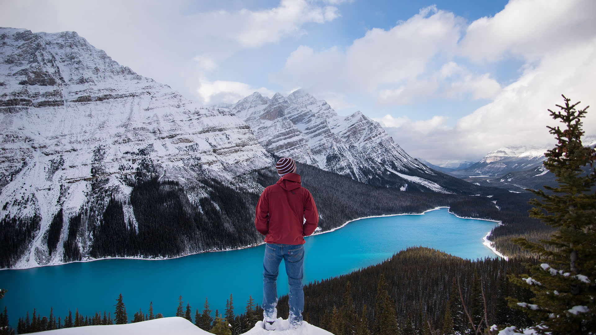 A man stands with the world at his feet, surrounded by snowy mountains and a sparkling blue lake