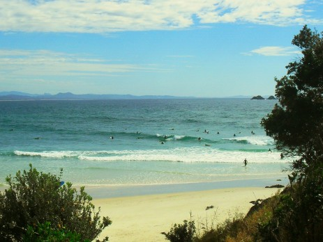 Beach scene of surfers riding the waves in the iconic town of Byron Bay