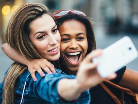 Two girls posing for a selfie shot in a city