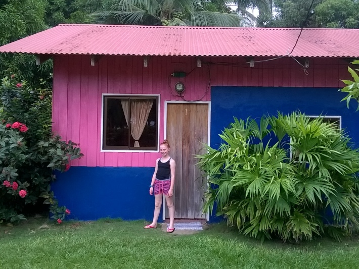 Girl standing in front of Costa Rica pink volunteer hut