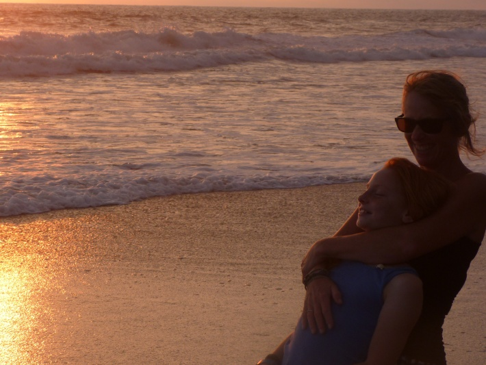 Mother and daughter on beach laughing and smiling in Costa Rica sunset