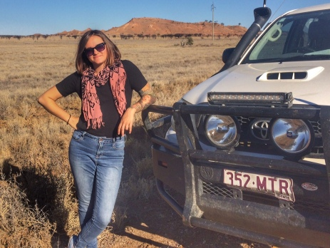 Alysha leaning on the bonnet of a ute with a rugged outback scene of rocks and dessert in the background