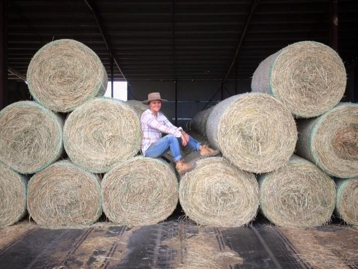 Girl sitting on hay bales