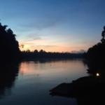 The sun sets over the river in Borneo
