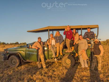 Game ranger participants in South Africa pose next to their game vehicle