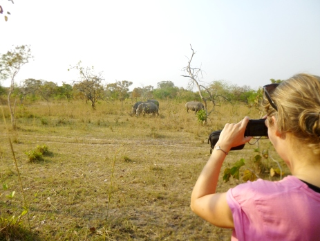 Volunteer in Uganda collects data about rhinos, stopping for a quick photo