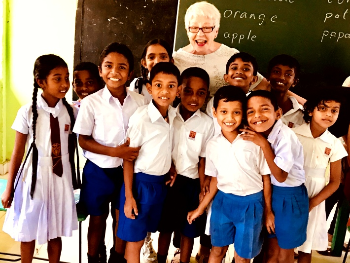 A volunteer teaches English to children in a school in Sri Lanka