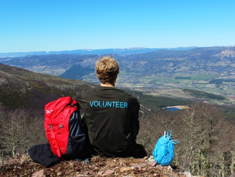 Volunteer with his back to the camera wearing an Oyster t-shirt looks out over the mountains of Chile. There is a backpack to his left and bag to his right as he sits