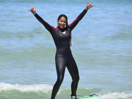 Girl on a surfboard with hands in the air mastering standing up