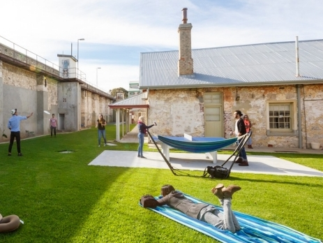 View from the communal outside area at Freemantle prison YHA in Western Australia. Backpackers enjoying the hammocks and playing games in the sunshine.