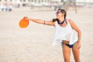 Spain, Cadiz, El Puerto de Santa Maria, Woman playing frisbee on the beach