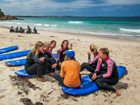 Group of surf students sitting on boards on the beach learning from an instructor with the ocean as the backdrop