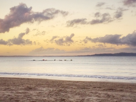 Sunset beach scene at Noosa's main beach with kayakers in the distance