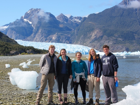 A group of British and American gap year volunteers in Chile, standing in front of a glacier and a mountain.